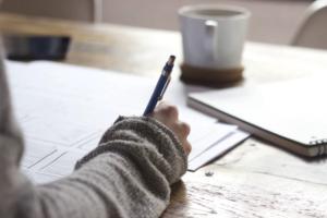 ペンで文字を書く女性の画像