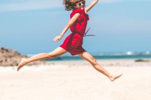 元気にジャンプをする赤い服の女性の画像